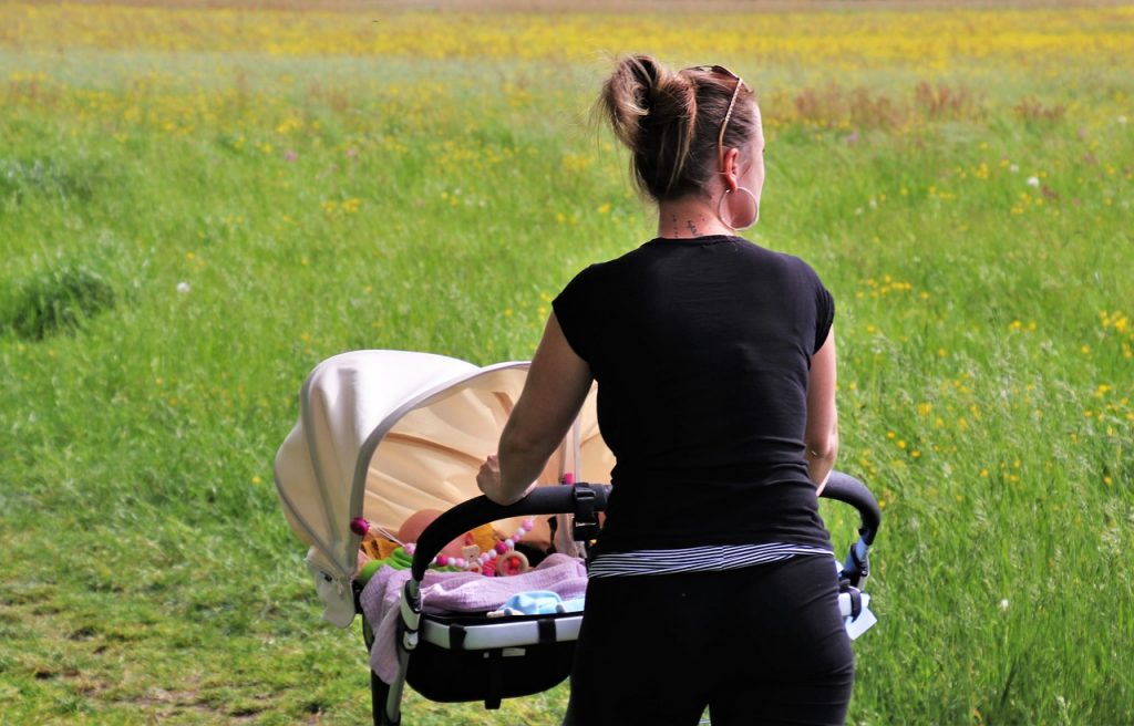 woman pushing a baby pram with bassinet