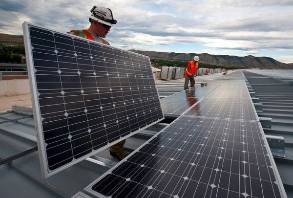 Two workers offering solar panel financing options