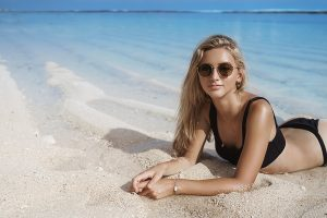 Blond woman on the beach wearing swimsuit