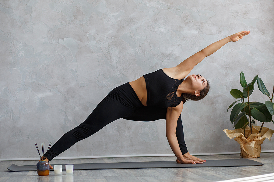 Woman taking online yoga courses at home